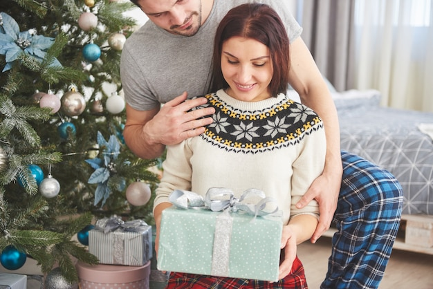 Young couple celebrating christmas. a man suddenly presented a present to his wife. the concept of family happiness and well-being Premium Photo
