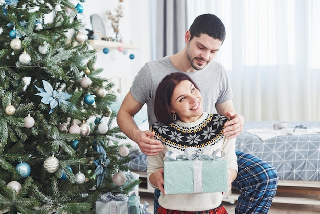 Young couple celebrating christmas. a man suddenly presented a present to his wife. Premium Photo