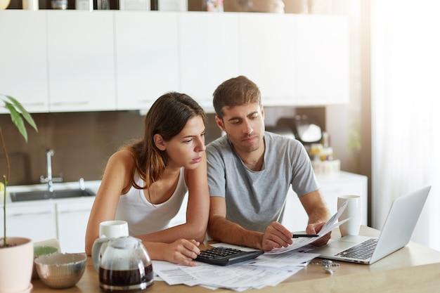 若いカップルが家族の予算をチェック 無料写真