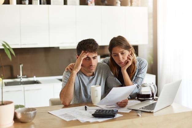 Молодая пара проверяет свой семейный бюджет Бесплатные Фотографии