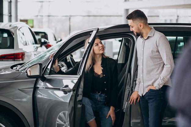 Молодая пара выбирает автомобиль в автосалоне Бесплатные Фотографии