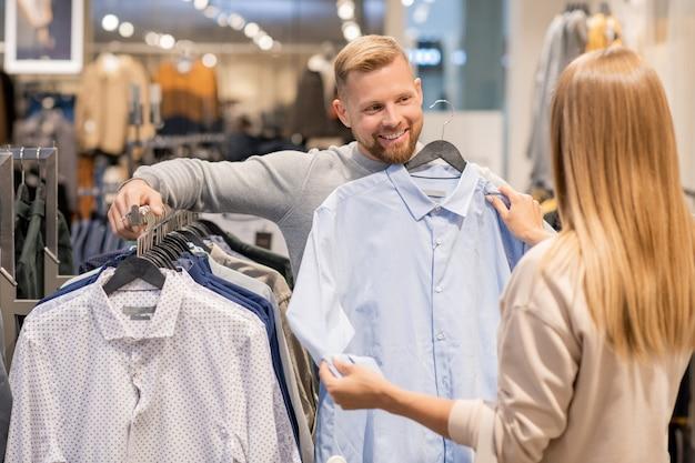 モールの衣料品部門の新しいコレクションでラックに立っている間男のための新しいシャツを選択する若いカップル Premium写真