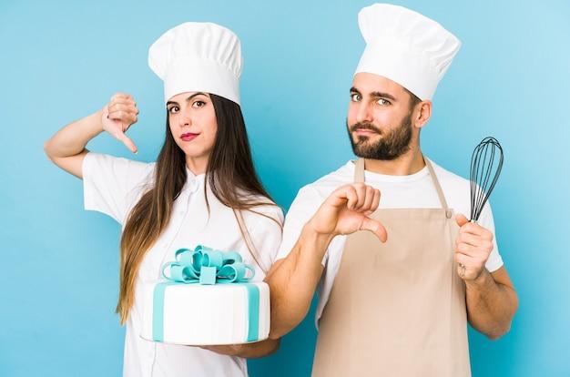 若いカップルが一緒にケーキを調理する嫌いなジェスチャーを示す孤立した親指ダウン。 Premium写真