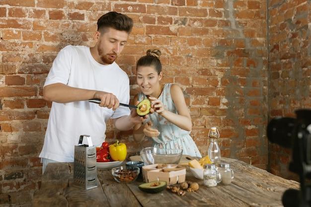 Giovane coppia che cucina e registra video dal vivo per vlog e social media Foto Gratuite