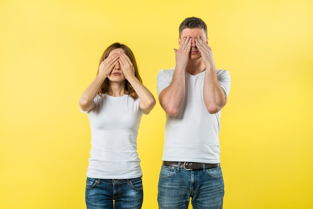 Young couple covering their eyes against yellow background Free Photo