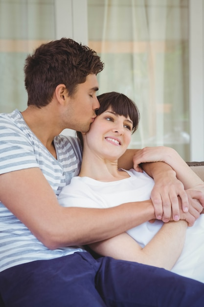 Young Couple Cuddling On Sofa In Living Room Photo | Premium ...