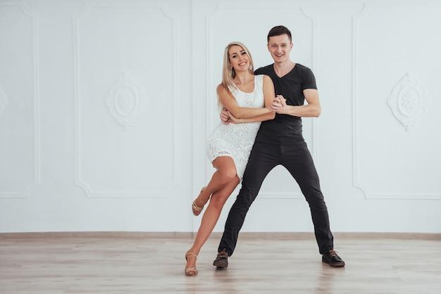 Young couple dancing latin music: bachata, merengue, salsa. two elegance pose on white room Premium Photo