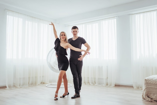 Young couple dancing latin music: bachata, merengue, salsa. two elegance pose on white room Premium Photo