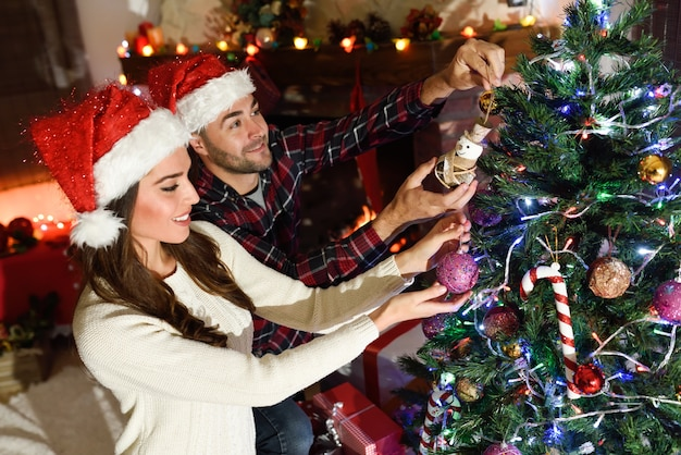 young couple decorating christmas tree free photo