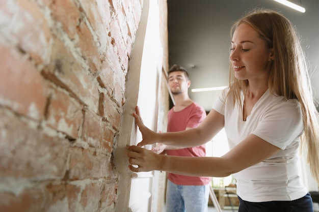 Young couple doing apartment repair together themselves. married man and woman doing home makeover or renovation. concept of relations, family, love. measuring the wall, preparing for design. Free Photo