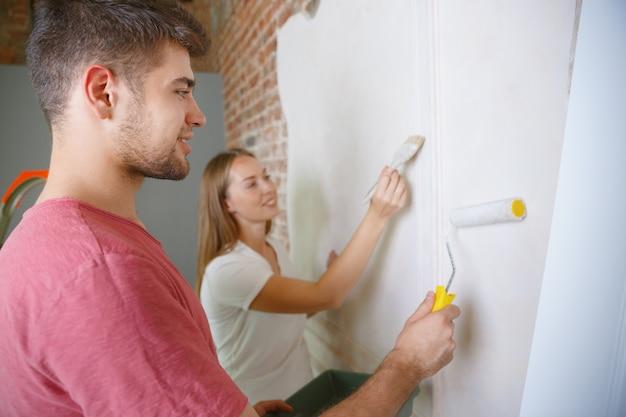 Giovani coppie che fanno insieme la riparazione dell'appartamento. uomo e donna sposati che fanno rifacimento o ristrutturazione della casa. concetto di relazioni, famiglia, amore. dipingere il muro insieme e ridere. Foto Gratuite