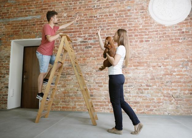 Giovani coppie che fanno insieme riparazione dell'appartamento. uomo e donna sposati che fanno rifacimento o ristrutturazione della casa Foto Gratuite
