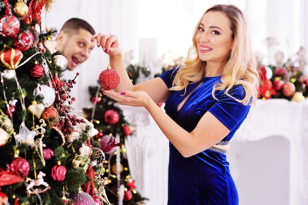 A young couple dresses up a christmas tree-a woman hangs toys on the tree Premium Photo