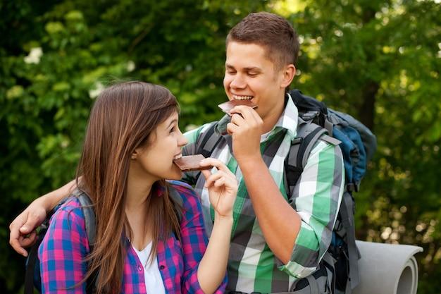 森でチョコレートを食べる若いカップル 無料写真