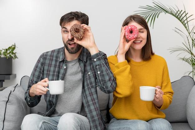 ドーナツを食べる若いカップル 無料写真