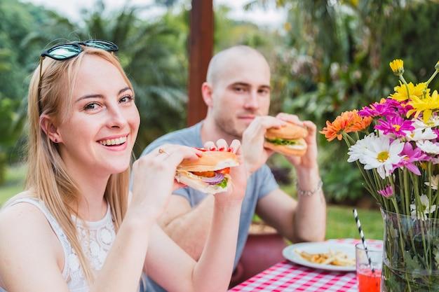 屋外で食べる若いカップル Premium写真