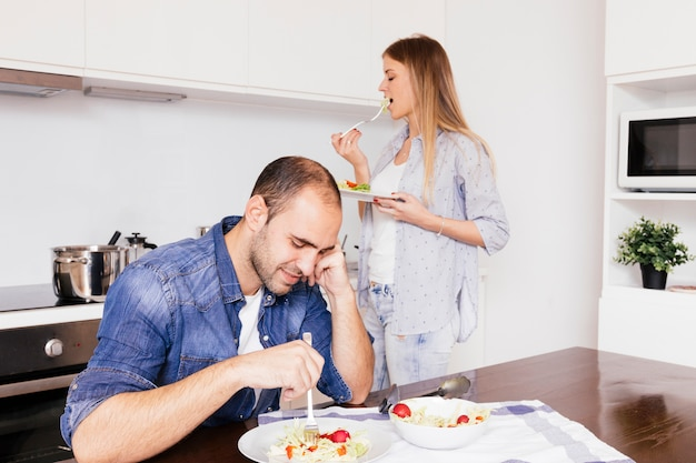 Young couple eating salad in the kitchen Free Photo