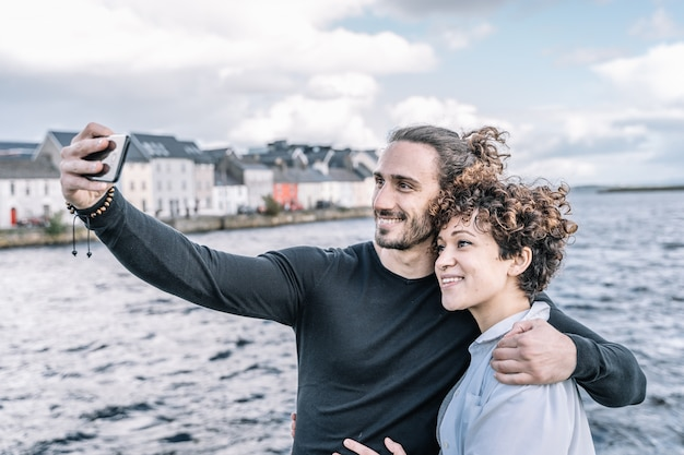 Young couple embraced by the shoulder making a selfie with the port and the sea out of focus Premium Photo