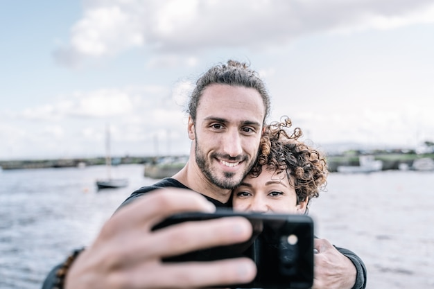 Young couple embraced by the shoulder making a selfie with the port and the sea out of focus Free Photo