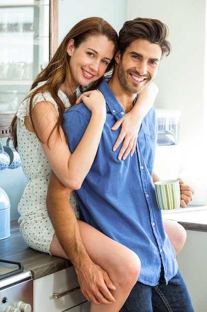 Young couple embracing in kitchen while having coffee Premium Photo