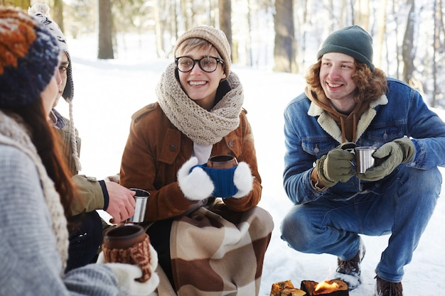 Young couple enjoying drinks in winter forest Free Photo