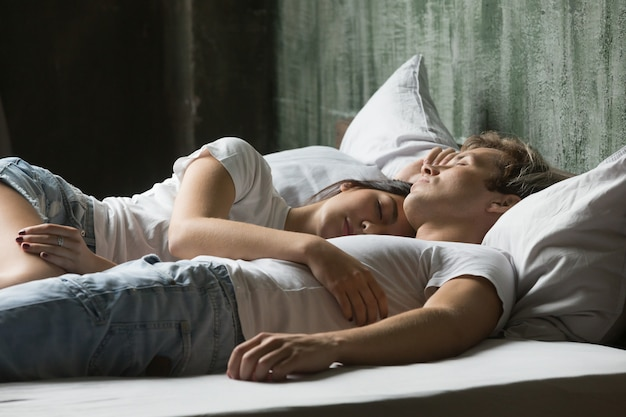 Young couple enjoying sleep on daytime lying in bed together Free Photo