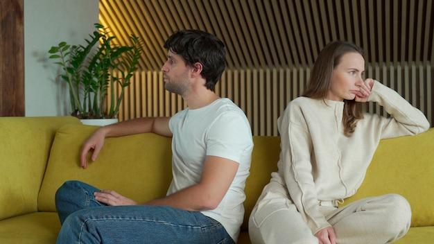 関係の問題を経験している若いカップルは、黄色いソファの上で家で隣同士に座っています Premium写真