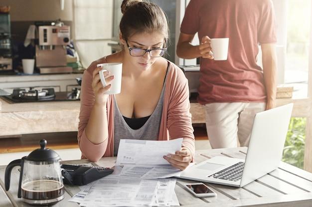 財政問題に直面し、キッチンで家計を管理する若いカップル。コーヒーを飲みながら一枚の紙を保持しているメガネのカジュアルな女性 無料写真