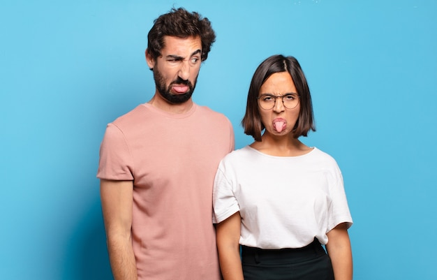 若いカップルは嫌悪感とイライラを感じ、舌を突き出し、厄介で厄介なものを嫌います Premium写真