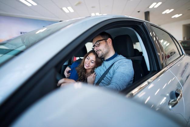 Giovani coppie che si sentono sani e salvi nella loro nuova auto Foto Gratuite