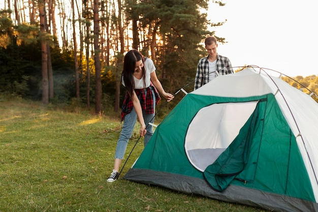 Young couple fixing tent in the nature Free Photo