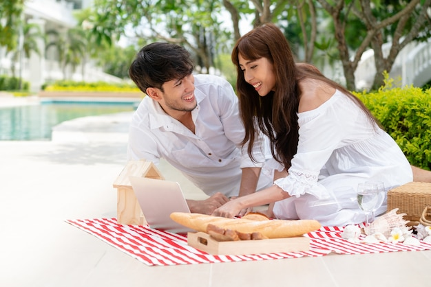 Young couple go picnic at the park in summer. Premium Photo