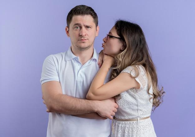 Молодая пара счастливая женщина, глядя на своего любимого мужчину, собираясь поцеловать синий Бесплатные Фотографии
