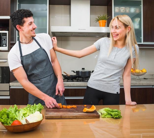 부엌에서 야채를 절단하는 동안 재미 젊은 부부 무료 사진