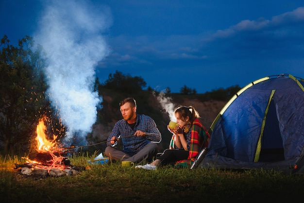 Young couple having a rest at bonfire beside camp and blue tourist tent, drinking tea, enjoying night sky. Premium Photo