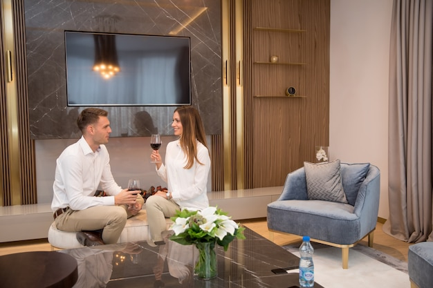 Young couple having a romantic evening with a glass of red wine at home in the contemporary living room Premium Photo