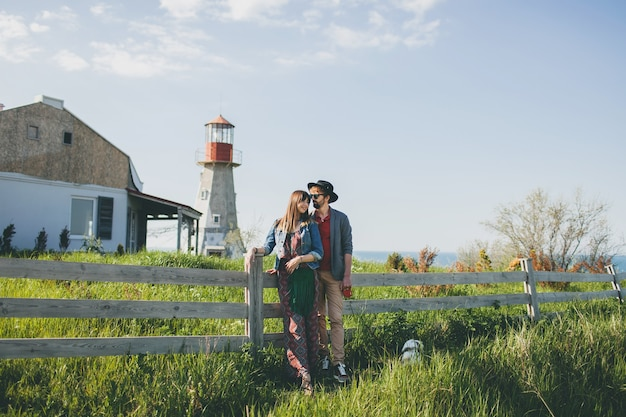 Young couple hipster indie style in love walking in countryside, holding hands, lighthouse on background, warm summer day, sunny, bohemian outfit, hat Free Photo
