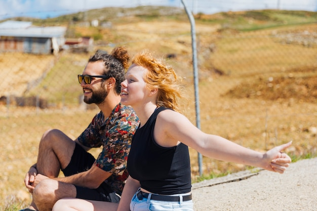 Young couple hitchhiking on roadside Free Photo