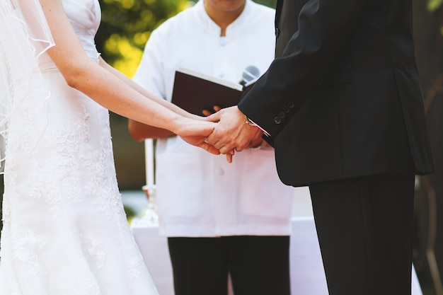 Young couple hold hand at wedding ceremony Premium Photo