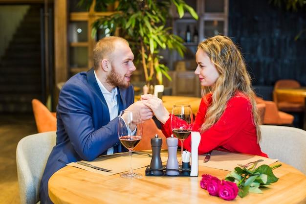 테이블에서 손을 잡고 젊은 부부 무료 사진