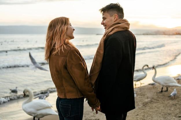 Coppia giovane mano nella mano sulla spiaggia in inverno Foto Gratuite
