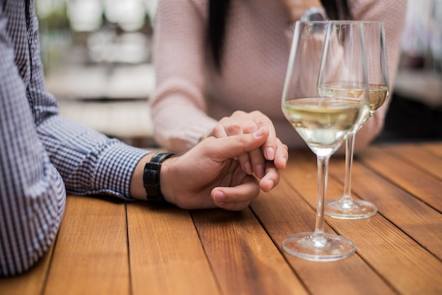 Young couple holding hands at the cafe, closeup. Premium Photo