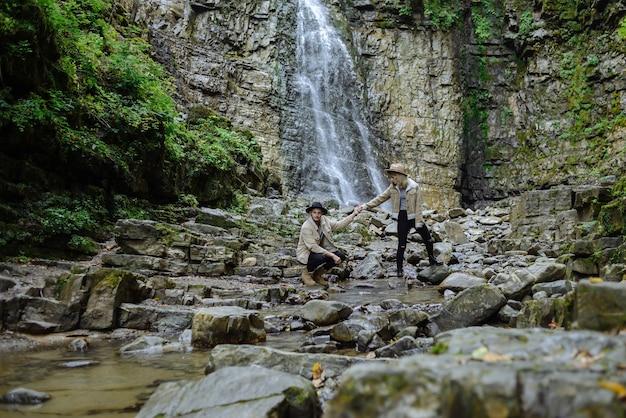 若いカップルが手をつないで、男は石の上に少ししゃがみました。若い男と女が森の小川を渡る。 Premium写真