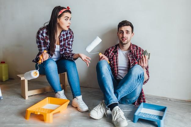 Young couple holding paint rollers and smiling each other while having break during repairment Premium Photo