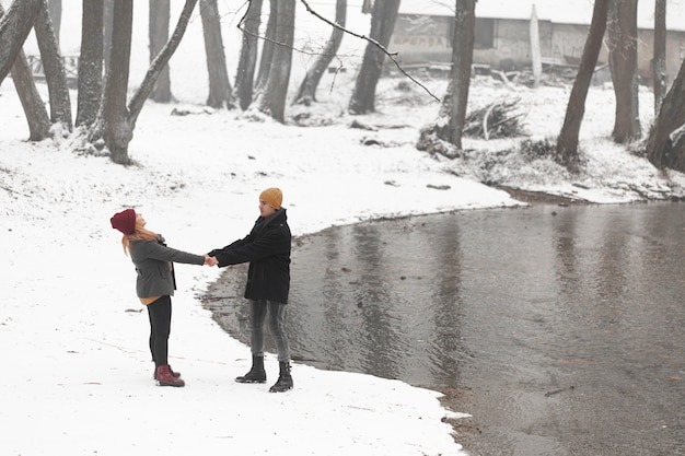 Young couple holding their hands next to a river Free Photo