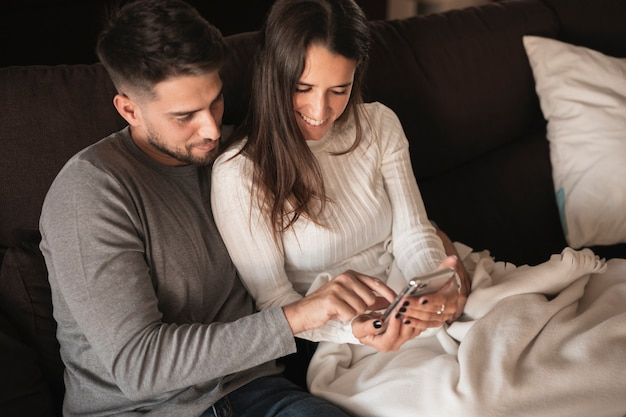 Young couple at home looking on mobile Free Photo