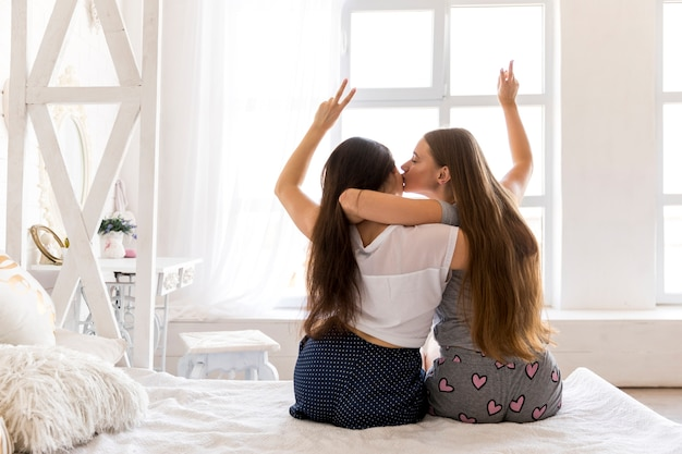 Young couple hugging and doing peace sign Free Photo