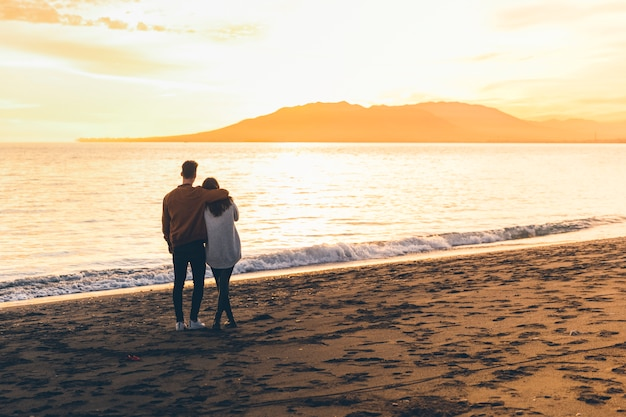 Young couple hugging on sea shore Free Photo
