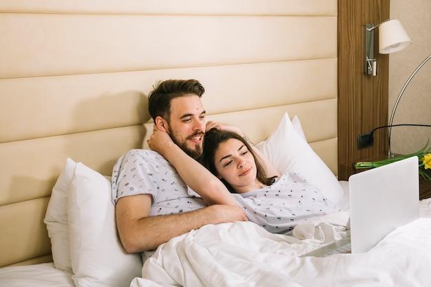 ラップトップを使用してベッドで若いカップル 無料写真