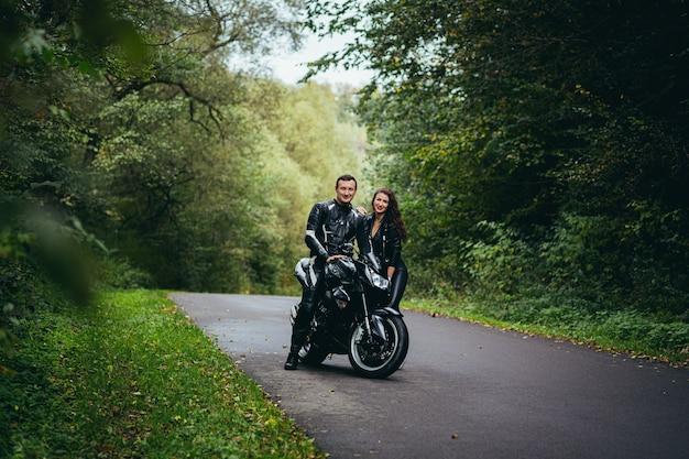 Молодая влюбленная пара в черной кожаной одежде возле черного спортивного мотоцикла на дороге Premium Фотографии